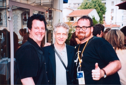 Demarbre at the 2002 Cannes Film Festival with filmmaker David Cronenberg (centre) and actor Josh Grace (left)