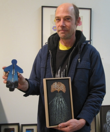 Stotik displaying two paintings he created using unconventional materials: at left, a wooden angel from a craft store; at right, a rice sack (photo by Anita Malhotra)