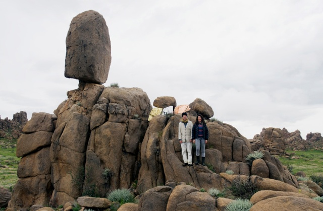 "Bruce Conkle and Marne Lucas posing on ""Balance Rock - Miner Threat"" (metal leaf on granite)  in Mongolia's Gobi Desert in 2012 (photo by Maik Teriete)"