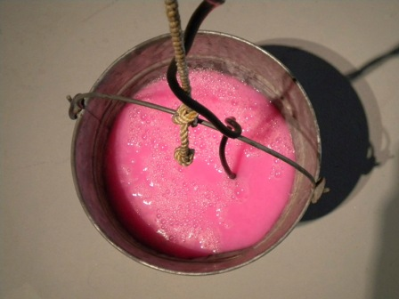 """Revolution"" (galvanized pail, rope, pepto bismol, pump) from Bruce Conkle's 2010 show ""Magic Chunks"" (photo by Marne Lucas)"