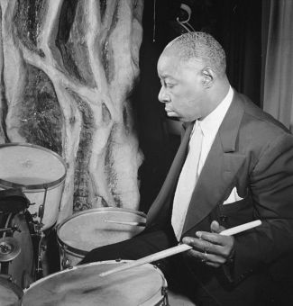 "Drummer Warren ""Baby"" Dodds (1898-1959) in New York City in 1946 (public domain photo by William P. Gottlieb)"