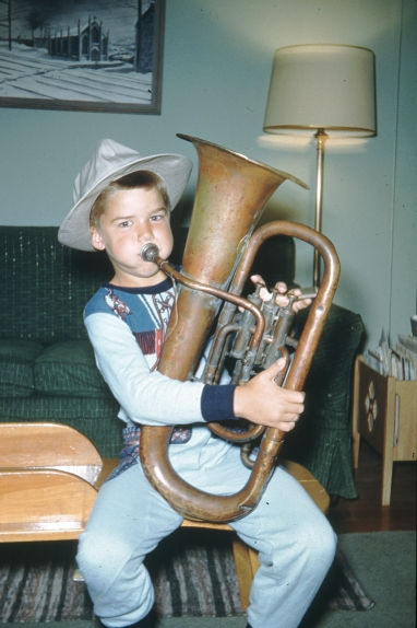 Frisell as a youngster in Denver, Colorado playing a euphonium that his grandfather, Wilhelm, used to play in a community orchestra. Behind him is a painting by his father, Olof (photo courtesy of Bill Frisell)