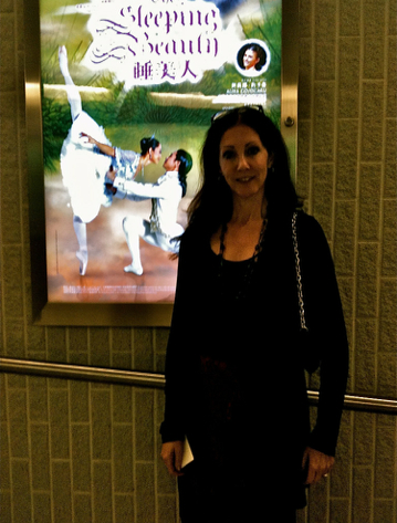 Cynthia Harvey in front of a Hong Kong Ballet poster for Sleeping Beauty