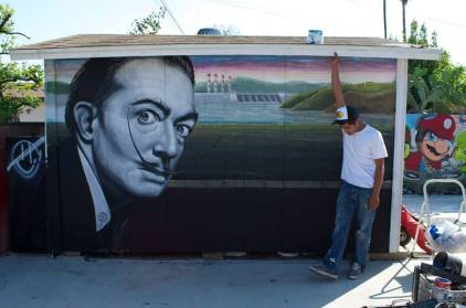 "Ponce with his mural ""Dali,"" a 2013 portrait of Salvador Dali (photo by Javier Martinez)"