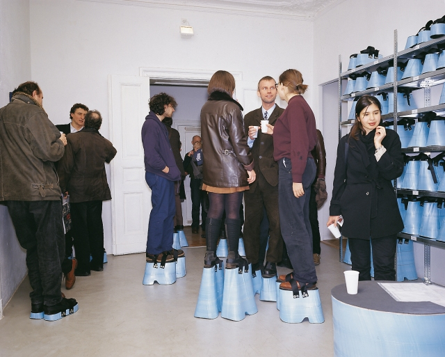 """level"" (1997), Styrodur/rubber/Velcro/measuring device, 50 pairs of platform shoes with heights of 5-43 cm, installation view at Galerie Gebauer Berlin, © Hans Hemmert and VG Bild Kunst"