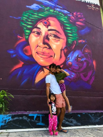 "Nasca Uno and two children in front of his mural ""Ibu Warung"" in Canggu, Bali, Indonesia in 2019 (photo courtesy of Nasca Uno)"