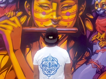 Nasca Uno in front of his mural at Lollapalooza Berlin , with his artist logo visible (photo by Anita Malhotra, Sept. 7, 2019)